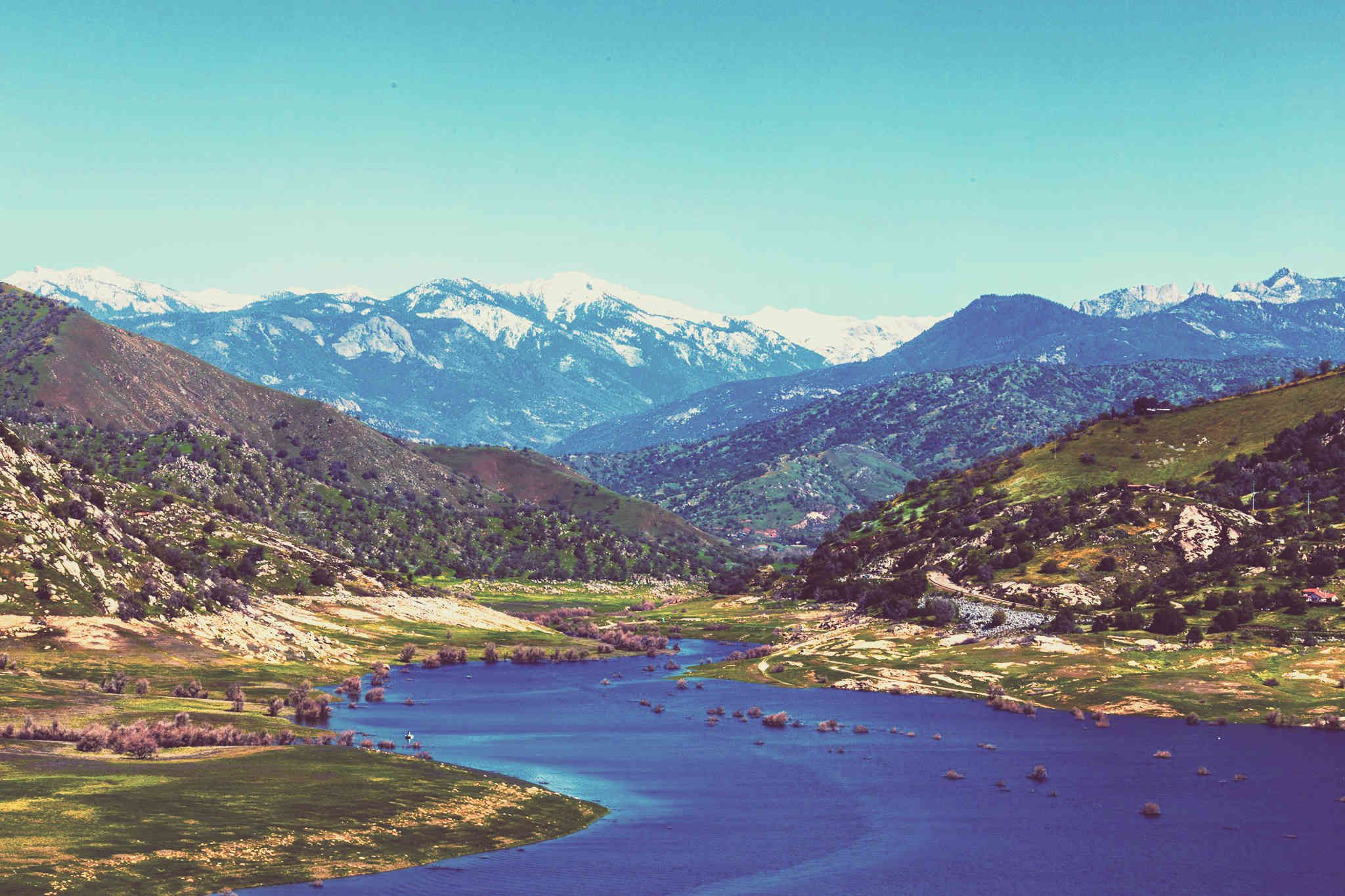 Long view of Kaweah Country - lake in foreground, hills mid-ground, Hig Sierra in the background.